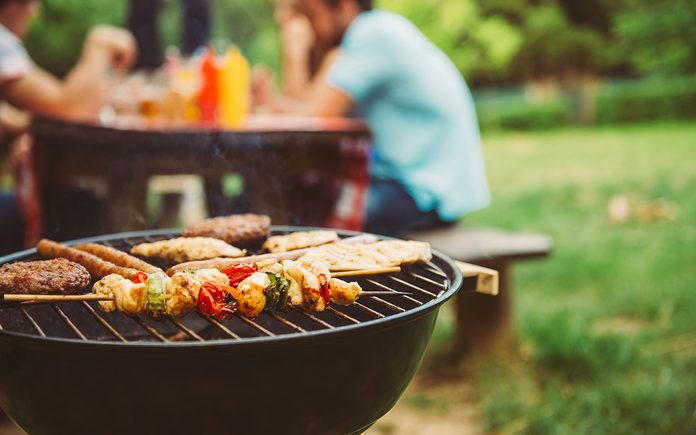 Friends making barbecue and having lunch in the nature.
