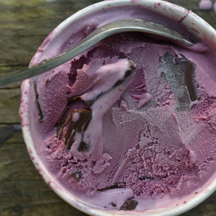 overhead view of a carton of black raspberry ice cream with chocolate chunks and spoon on wooden tabletop