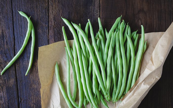 High Angle View Of Green Beans With Wax Paper On Wooden Table