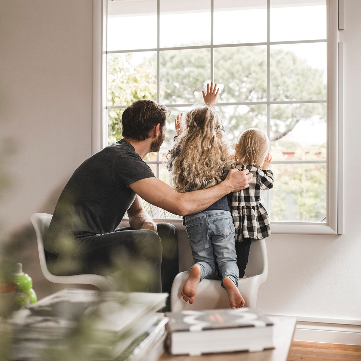 Father and two small kids looking out a window together