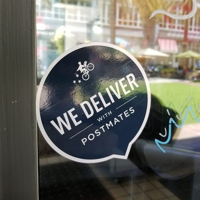 Close-up of logo reading We Deliver With Postmates, referencing the Postmates food delivery app service, on a restaurant window in the Silicon Valley, San Jose, California, June 7, 2018. (Photo by Smith Collection/Gado/Getty Images)