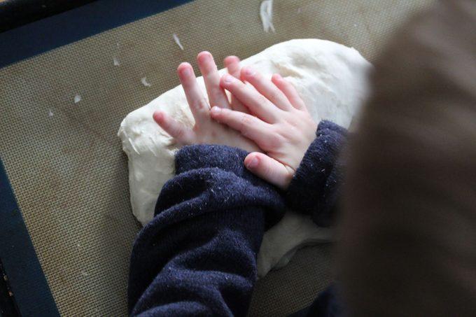 Child hands kneading dough
