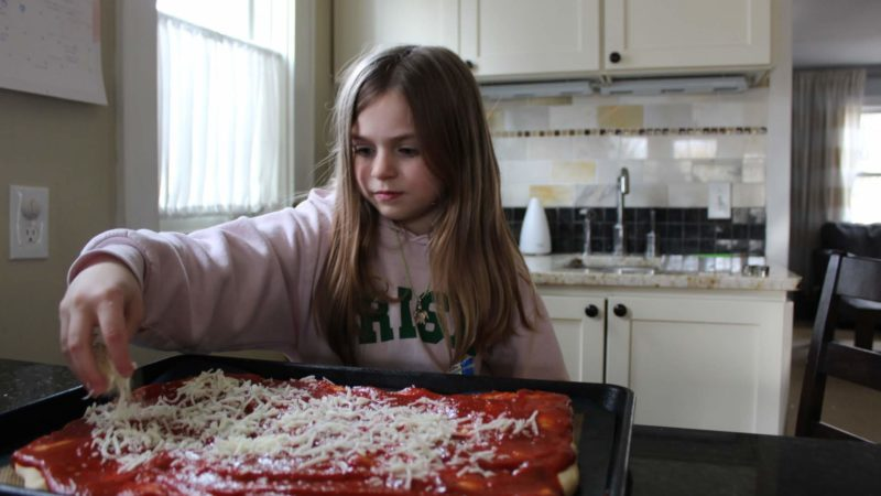 Girl spreading cheese on a pizza