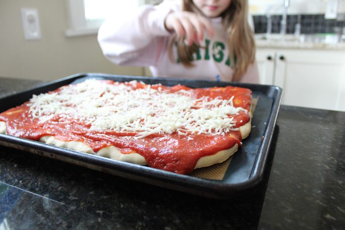 Child spreading cheese over sauce on pizza