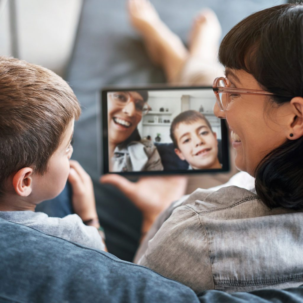 Rearview shot of a mother and her little son using a digital tablet together at home