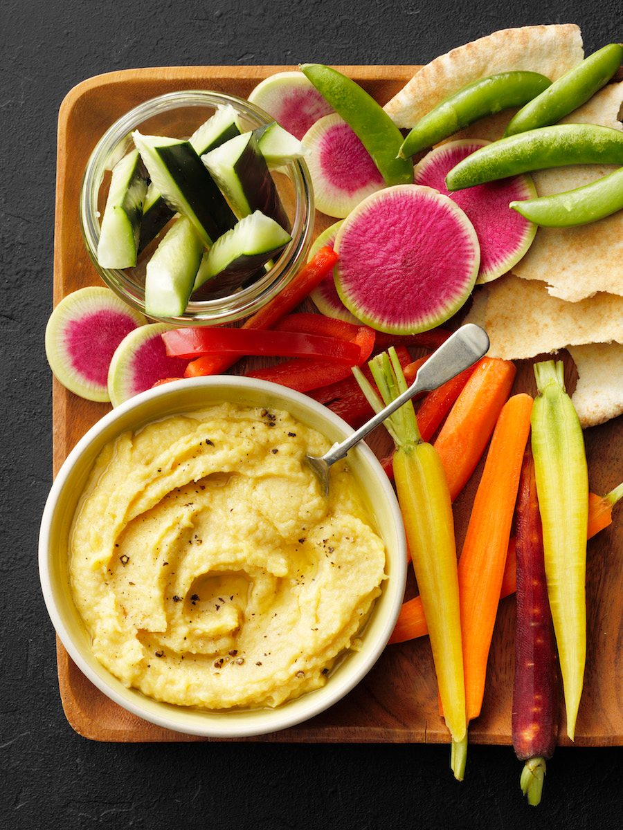 Easy hummus recipe; overhead camera angle; black textured surface; mixed veggies; watermellon radish; carrots; pea pods; pita bread; cucumber; shallow wooden serving tray; wood tray; wooden tray
