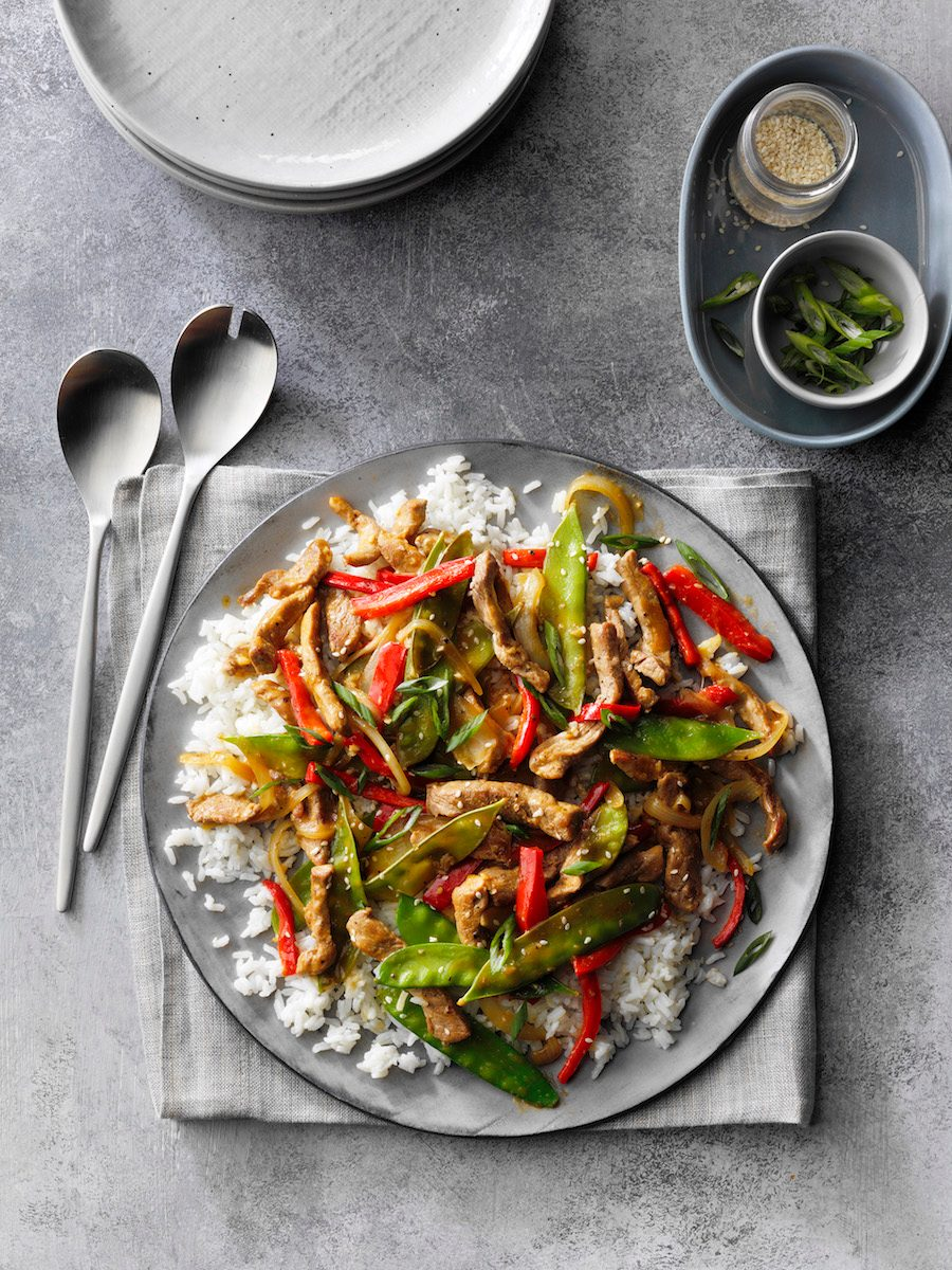 Ginger Pork Stir-Fry; overhead camera angle; mottled grey Russian surface; Grey linen cloth; grey folded napkin; salad serving forks; Grey plate stack; green onions; sesame seeds; snow peas; sweet red pepper; white rice