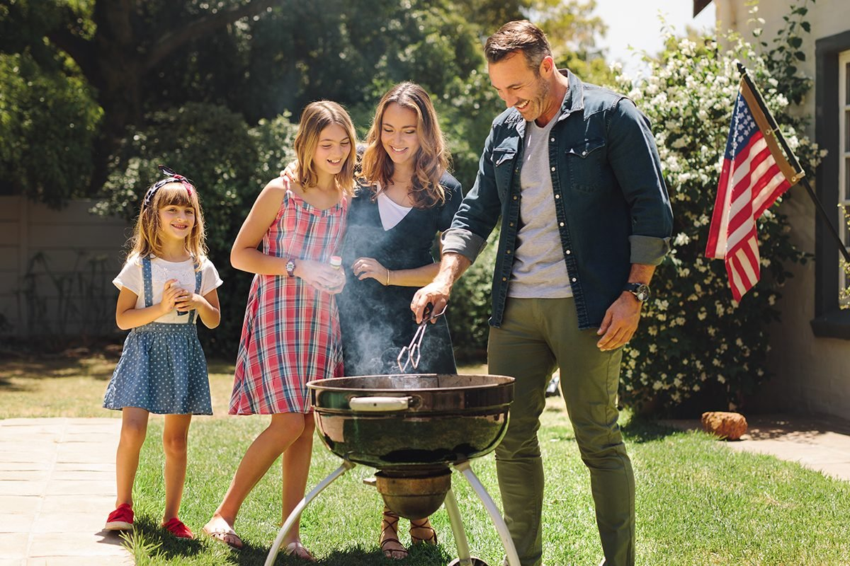 Family having fun cooking food together in their backyard. Man making barbeque standing in their backyard with wife and kids.