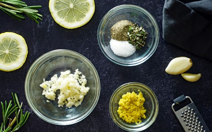 rub ingredients for grilled salmon in individual bowls on a slate counter