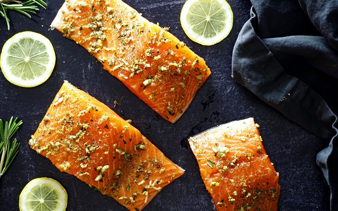 raw salmon filets with a lemon rosemary rub applied to their flesh on a slate background