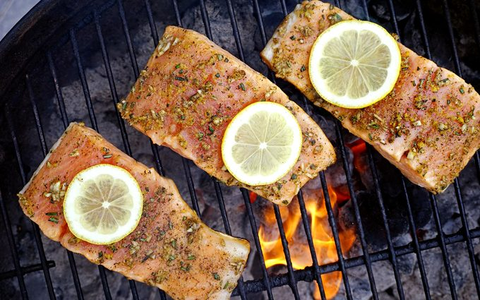 three grilled salmon fillets topped with lemon slices cooked over a charcoal grill with flames