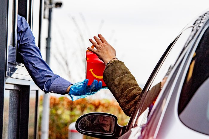 SCHIPHOL, NETHERLANDS - 2020/03/18: An employee wearing gloves as a protection seen giving food to a costumer at a McDonald's Mac Drive amid Coronavirus (Covid-19) fear. Netherlandss Health Ministry recorded a total of 2,460 infections, 76 death and 2 recovered since the beginning of the outbreak. (Photo by Robin Utrecht/SOPA Images/LightRocket via Getty Images)