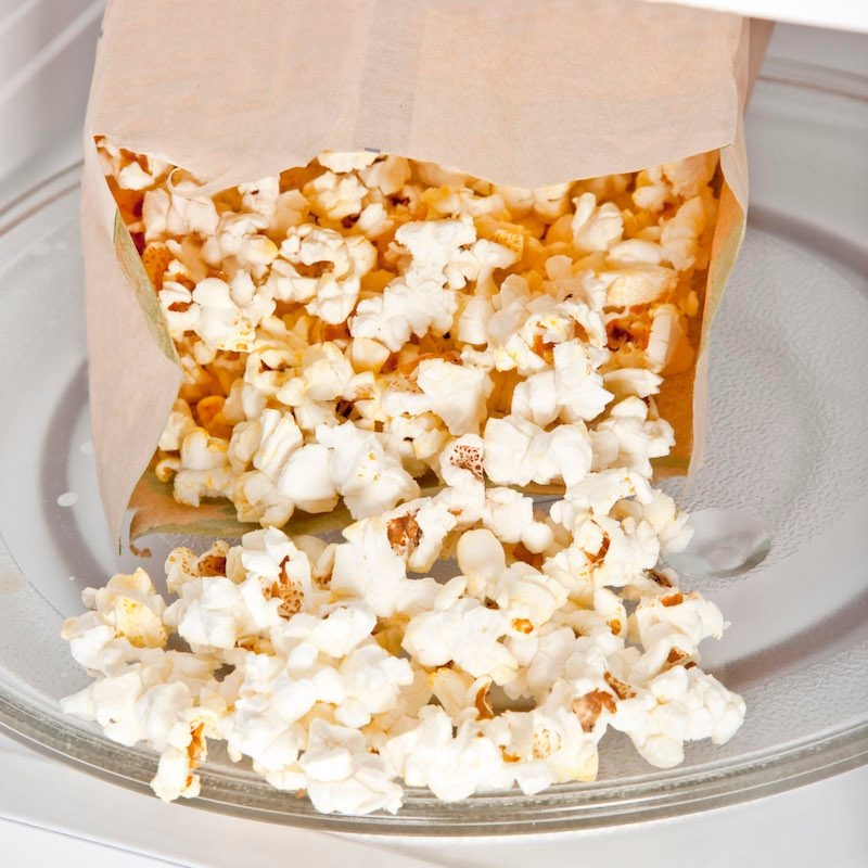 A batch of freshly popped homemade paper bag popcorn in the microwave.