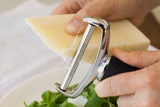 Man shaving Parmesan cheese onto salad