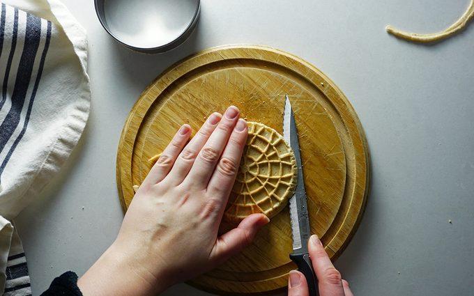 carefully cutting a stroopwafel in half