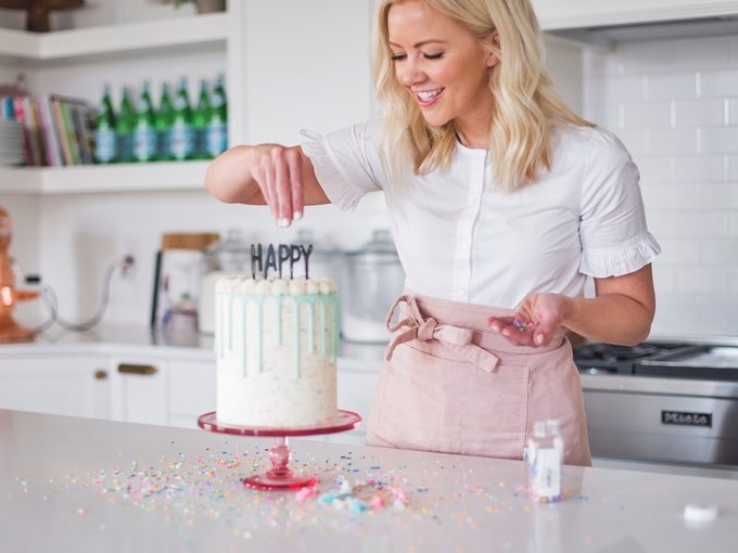 Blogger Courtney Rich decorates birthday cake on kitchen counter.