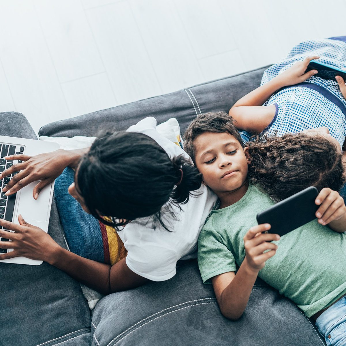 Young children together on couch playing on computers and phones