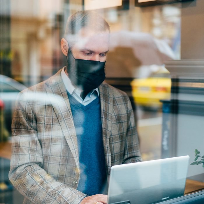 Businessman in cafe is wearing mask for protection against coronavirus