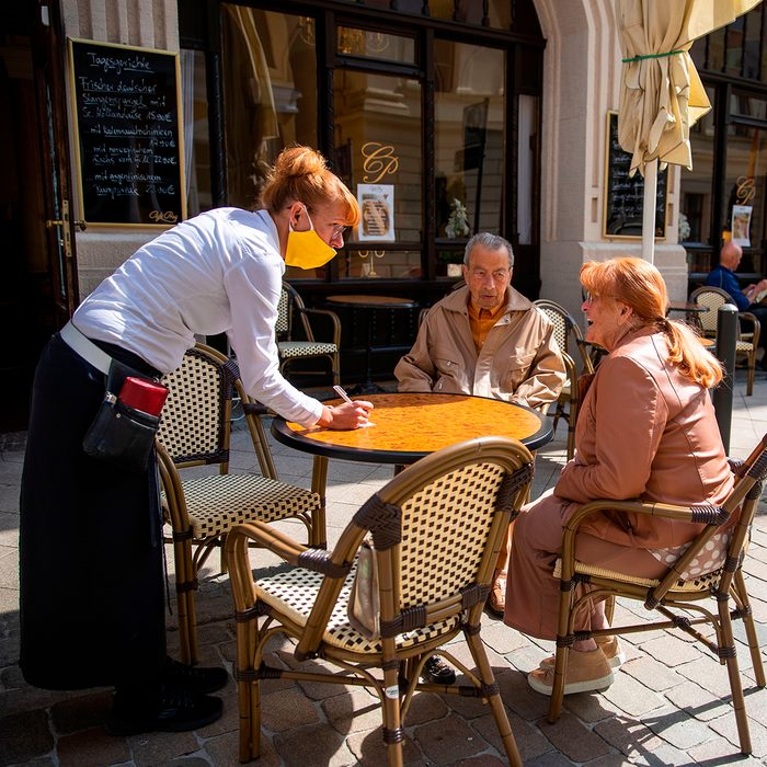 Waitress Stephanie Thiem (L) takes an order from guests Jens Krugmann (C) and Karin Fanselow (R) at the reopened Cafe Prag in Schwerin, northeastern Germany on May 9, 2020 amid the ongoing Covid-19, coronavirus pandemic. - The traditional cafe and restaurant welcomed sit in customers after two months of closure as restaurants in the state of Mecklenburg Western Pomerania were allowed to reopen under strict hygiene conditions Saturday, May 9, that saw a trickle of returning customers as the north eastern state and Germany are easing corona virus restrictions. (Photo by Odd ANDERSEN / AFP) (Photo by ODD ANDERSEN/AFP via Getty Images)