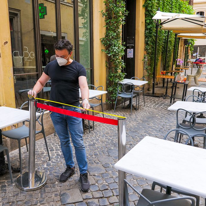 Rome, Italy, May 18 -- The owner of a pizzeria in the historic center of Rome near Piazza Navona measures the distance between the tables to ensure social distancing for the reopening of his restaurant after the end of the two month restrictions imposed by the lockdown for the Covid-19 crisis.