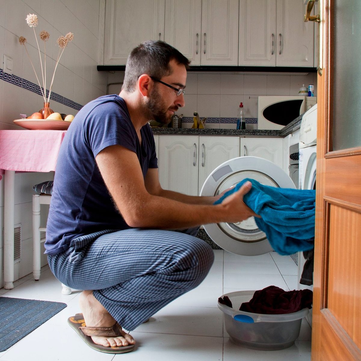 Man kneeling down and pulling laundry out of the machine