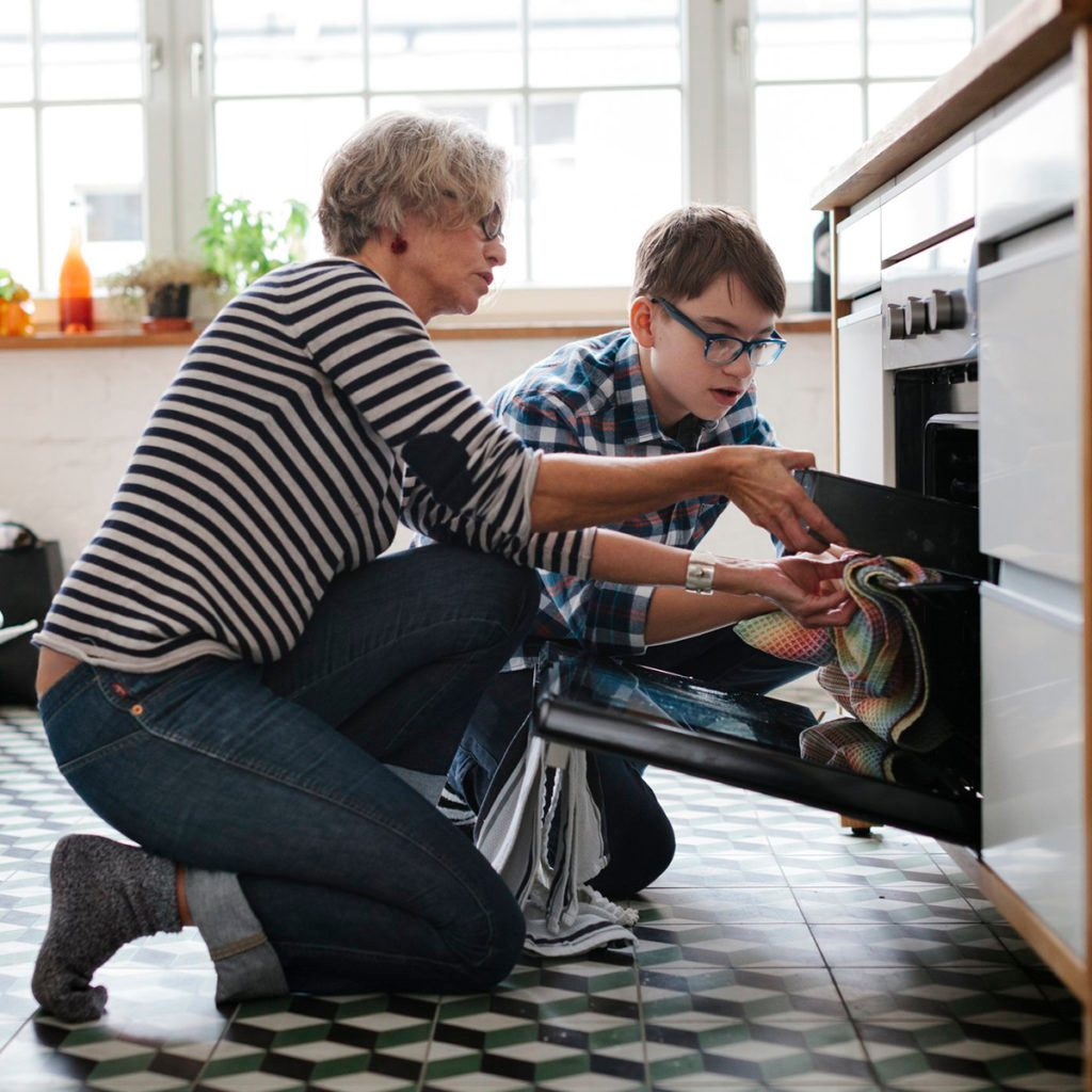Woman and boy pulling dish out of the oven