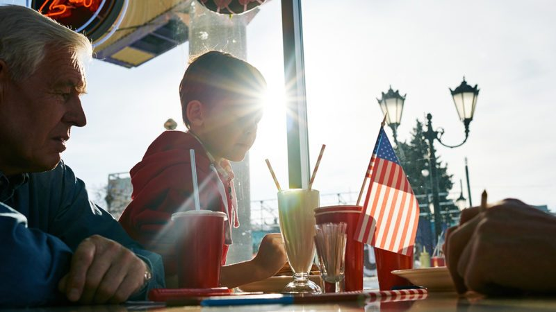 Grandfather and grandson having dinner at fast food cafe on fourth of July