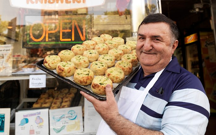 Yonah Schimmel standing outside his Lower East Side Knishery, proudly displaying his famous knishes.
