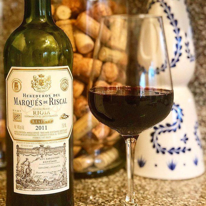 Marques de Riscal Rioja Reserva wine bottle with glass.