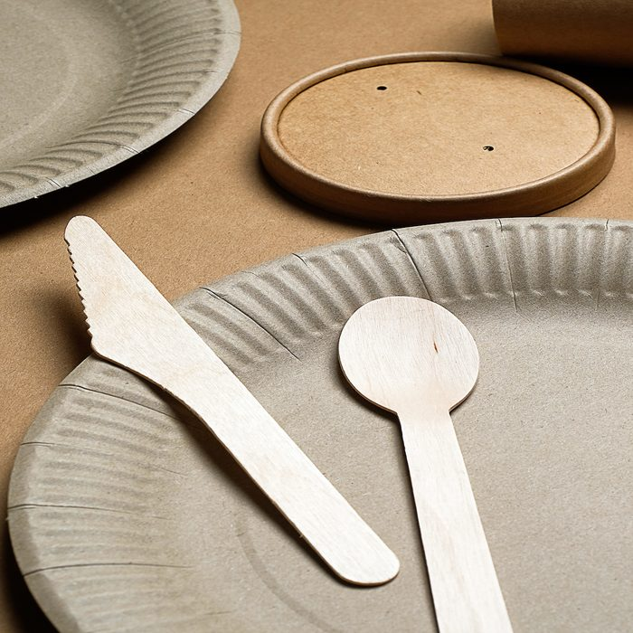 Disposable ECO-friendly tableware made of bamboo wood and paper on a cardboard background. The photo is covered in graininess and noise.