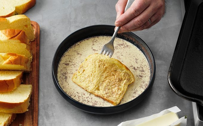 how to make french toast The Best French Toast; How to Step 4; flip and soak other side; half-and-half cream; egg yolks; brown sugar; vanilla extract; ground cinnamon; ground nutmeg; brioche bread; butter; maple syrup; fresh berries; whipped cream; confectioners' sugar; powder sugar; hands