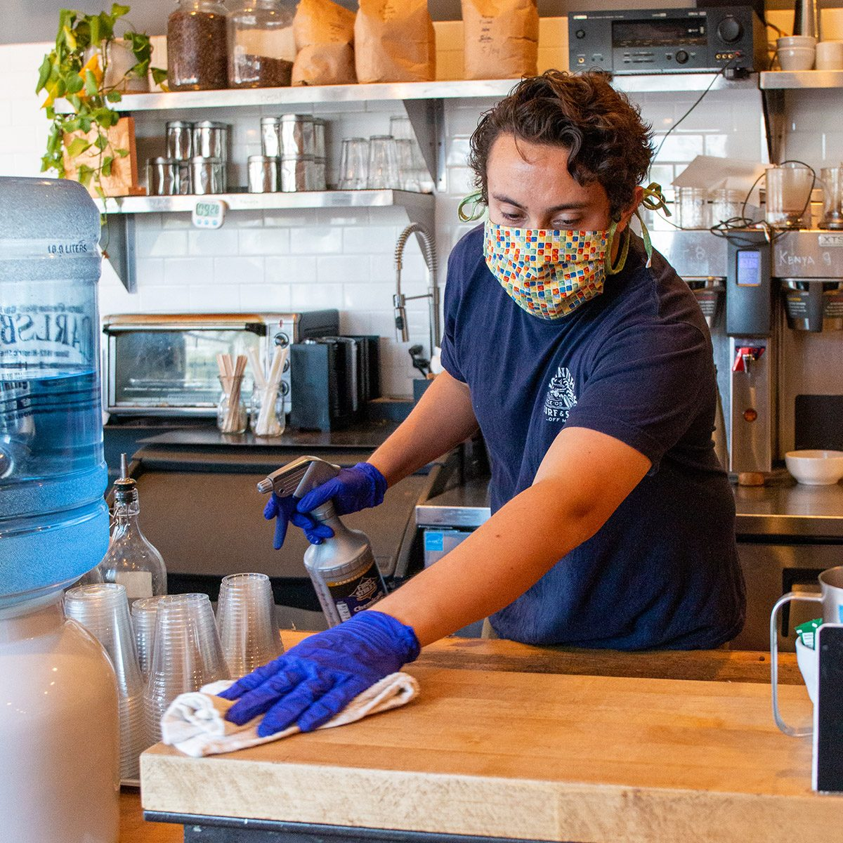 Man working in a coffee shop wearing a mask