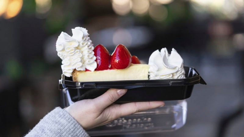 Strawberry Cheesecake from Cheesecake Factory in to go container being held in hand