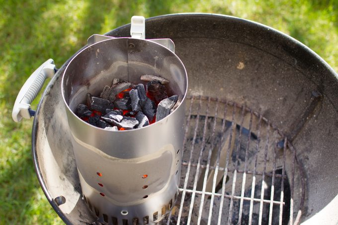 Chimney starter over charcoal grill.