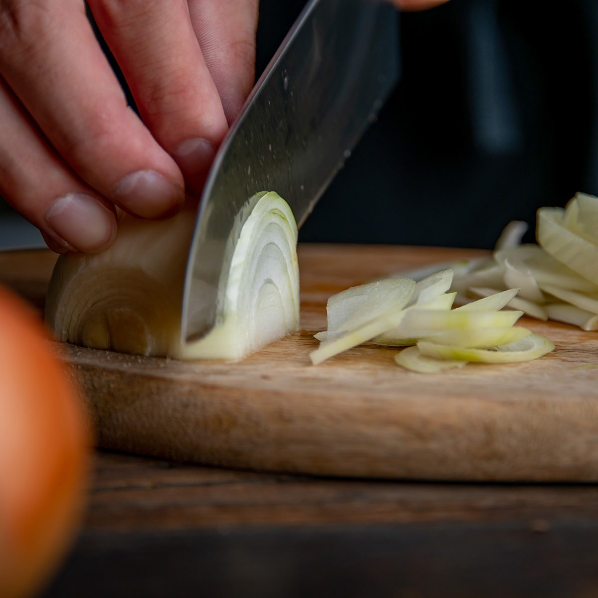 Slicing onion on cutting board in kitchen. Cooking image.