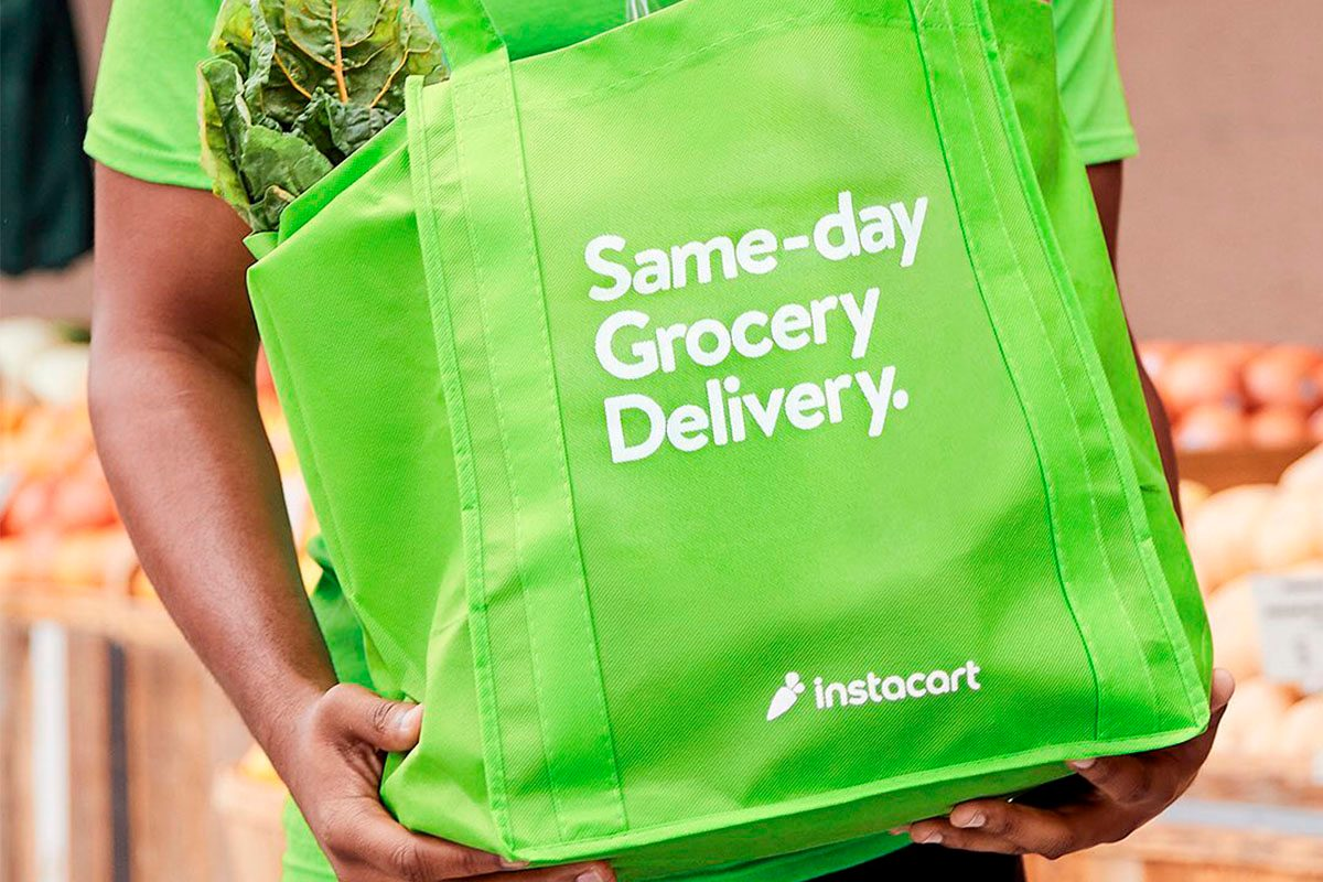 Man carrying groceries in green bag with Instacart advertising bag