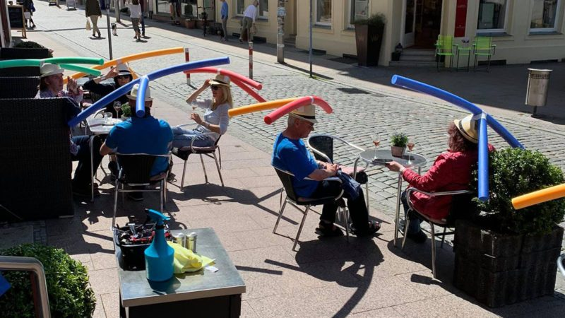 German cafe practicing social distancing with pool noodle hats.
