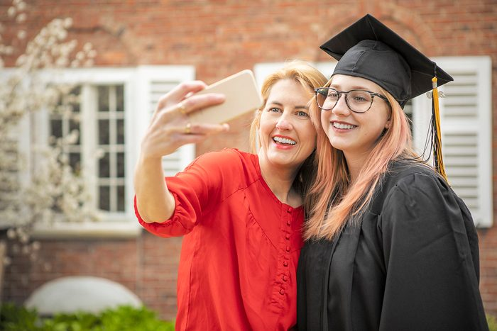 A 47 year old mother takes a selfie with her 18 year old high school graduate outdoors.