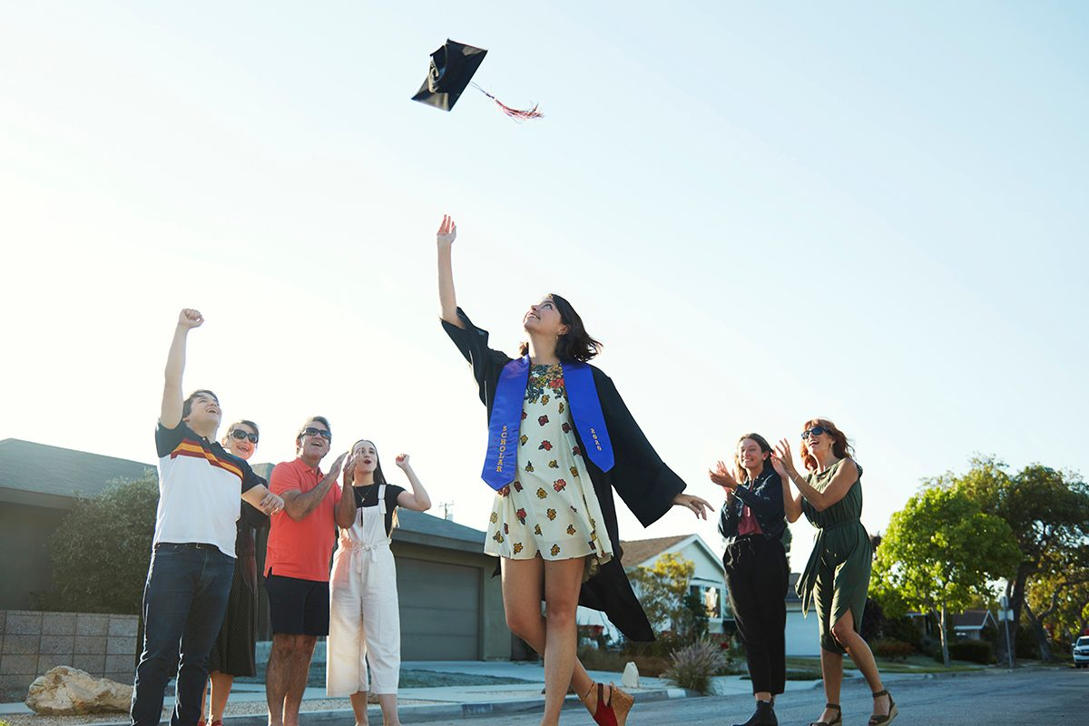 A 22 year old caucasian young woman dressed in a graduation gown throws her hat into the air surrounded by her friends and family in front of her home while celebrating her graduation from college
