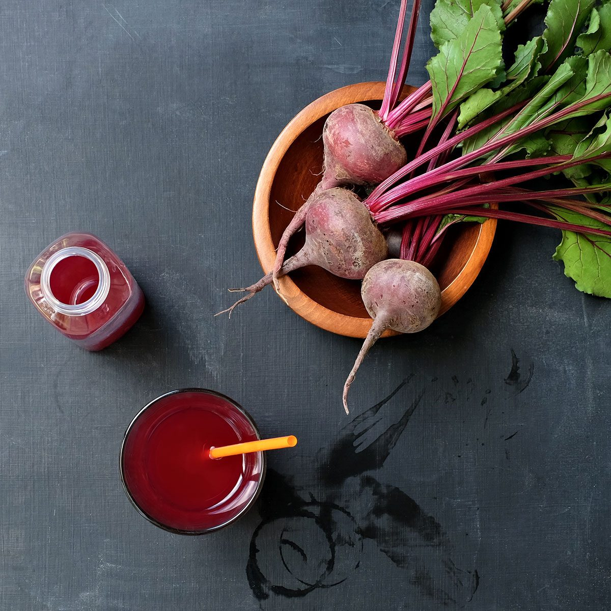 Healthy Beet Juice and Kombucha Drink on Messy Black Slate Table with Fresh Beets in Bowl