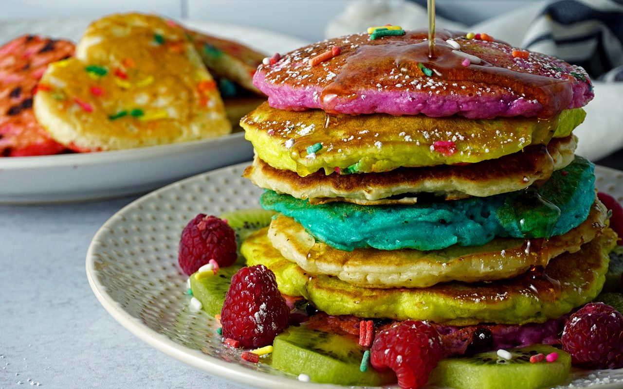 maple syrup poured over a stack of rainbow pancakes for kids