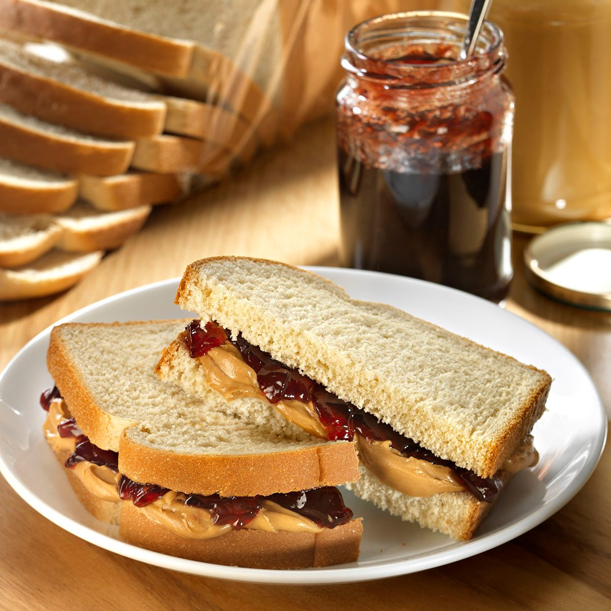 Peanut Butter and Jam sandwich on whole grain white bread with peanut butter jar and jam jar in background with loaf of bread and bottle of milk.