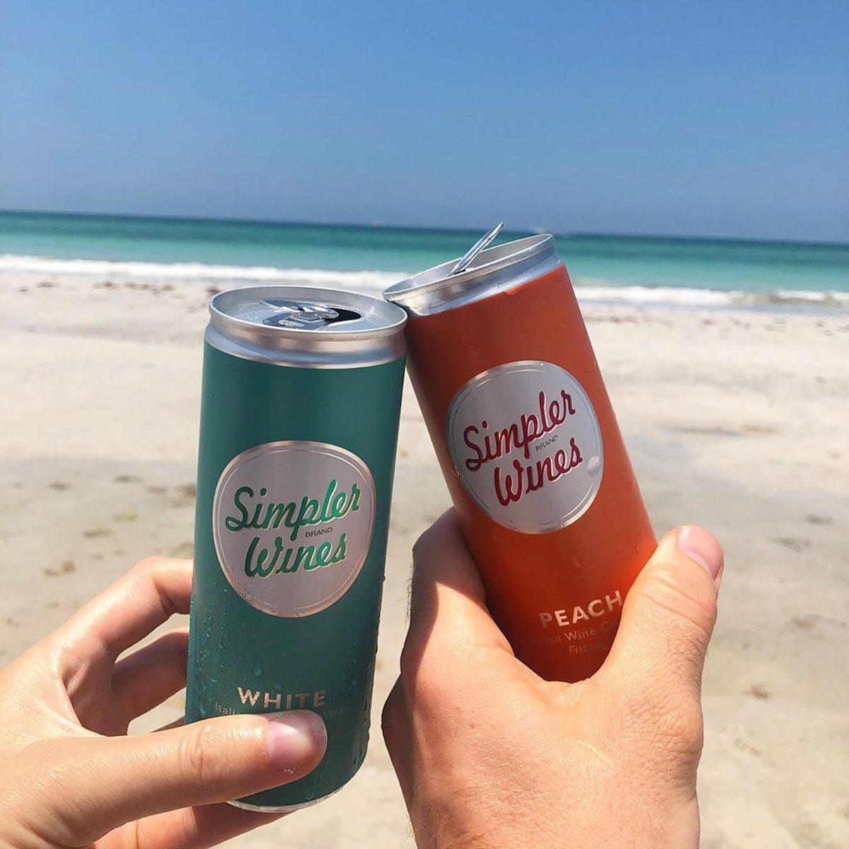 Simpler Wine cans cheersing on beach