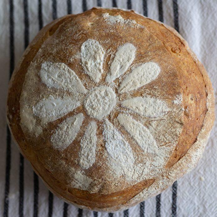 Round bread loaf with flower stencil.