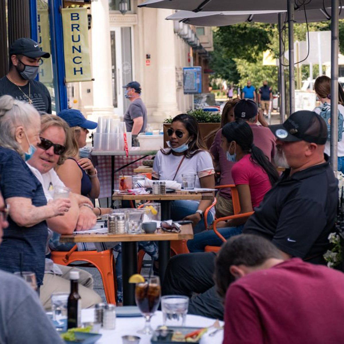 People eating outdoors at a busy restaurant