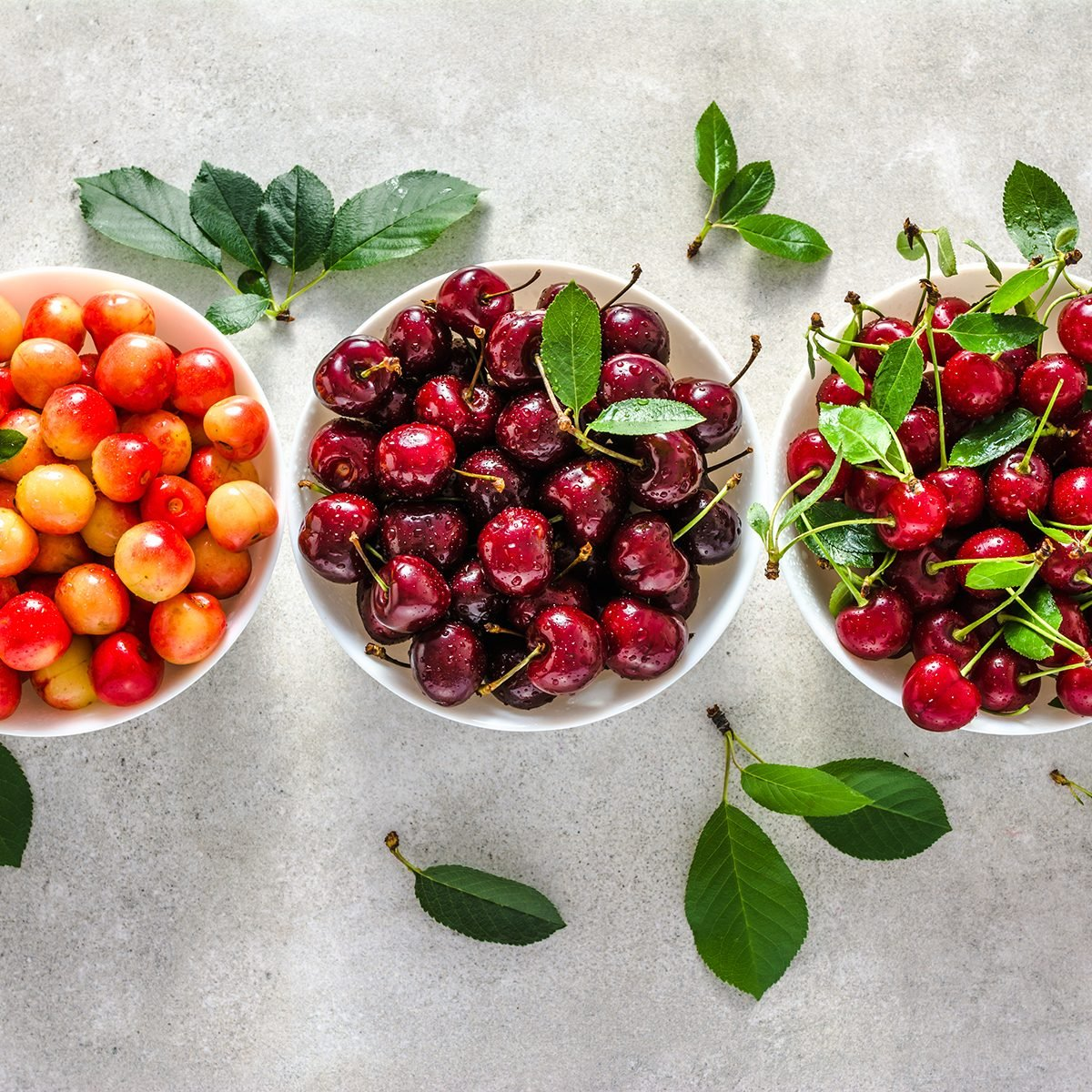 Different cherry on plate on white background, ripe cherries, sweet fruit, top view