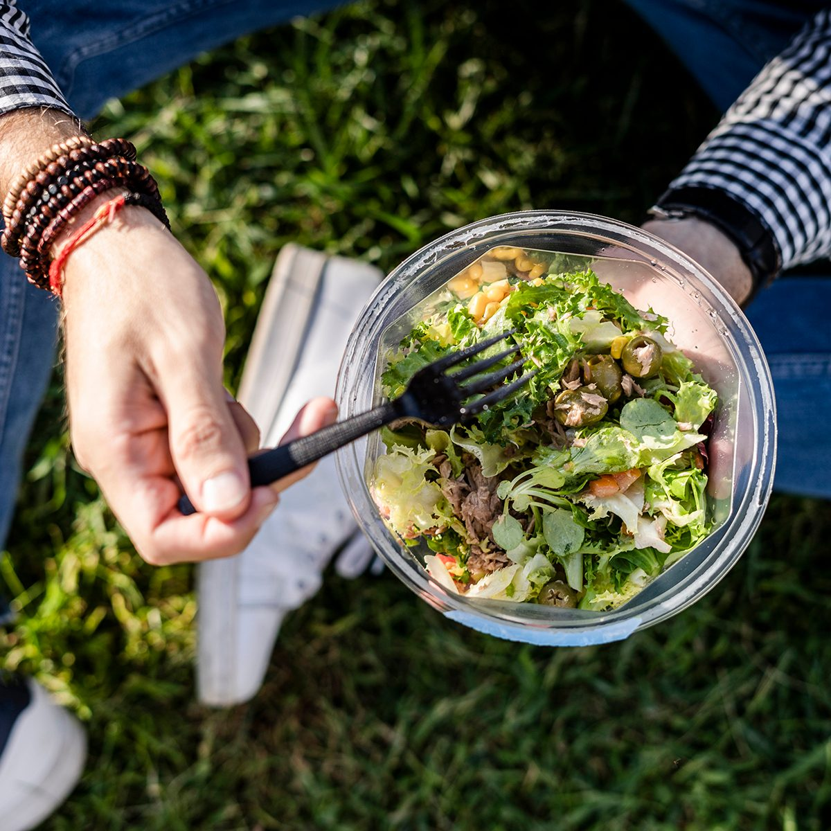 Person eating a salad in the grass