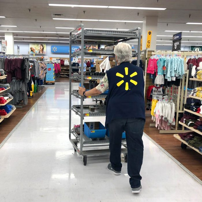 Walmart employee pushing a cart full of product down an aisle