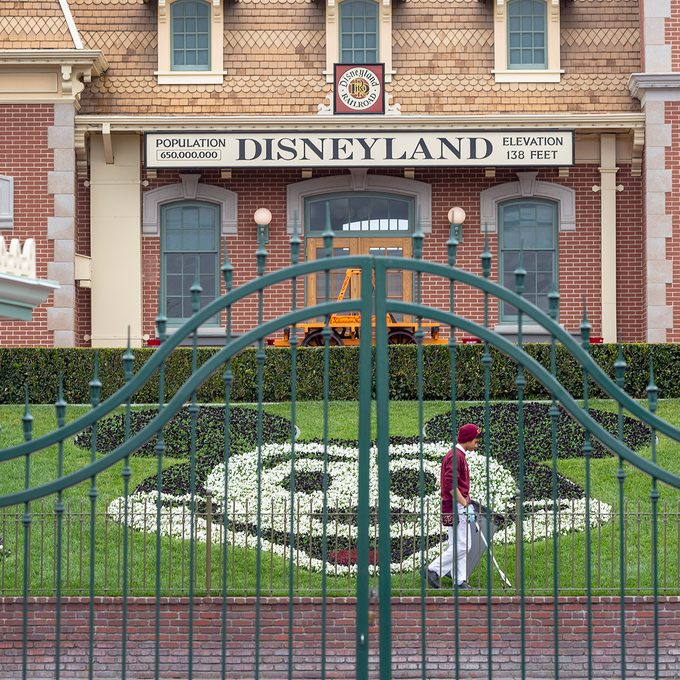 """An employee cleans the grounds behind the closed gates of Disneyland Park on the first day of the closure of Disneyland and Disney California Adventure theme parks as fear of the spread of coronavirus continue, in Anaheim, California, on March 14, 2020. - The World Health Organization said March 13, 2020 it was not yet possible to say when the COVID-19 pandemic, which has killed more than 5,000 people worldwide, will peak. """"It's impossible for us to say when this will peak globally,"""" Maria Van Kerkhove, who heads the WHO's emerging diseases unit, told a virtual press conference, adding that """"we hope that it is sooner rather than later"""". (Photo by DAVID MCNEW / AFP) (Photo by DAVID MCNEW/AFP via Getty Images)"""