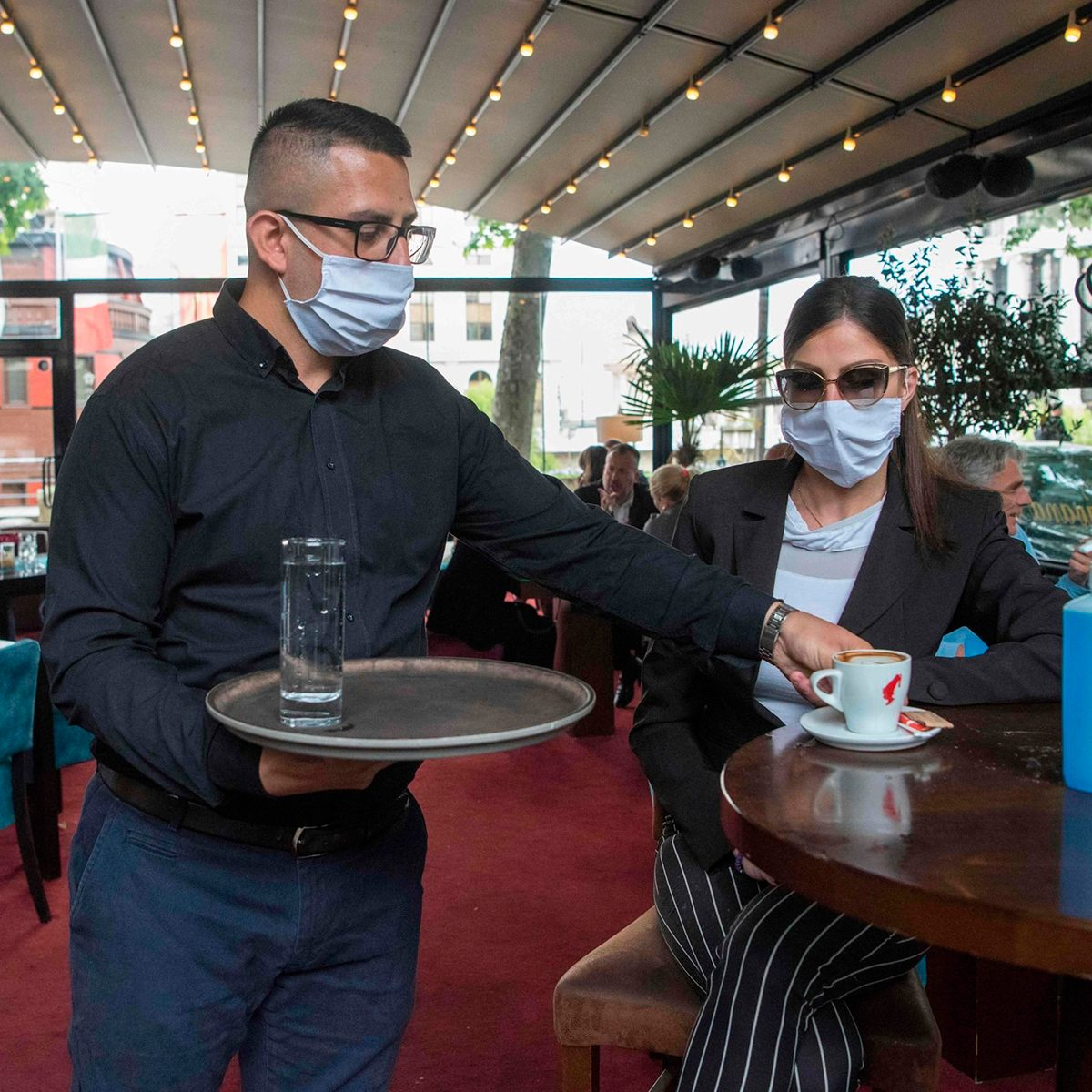 Masked waiter bringing coffee to guest